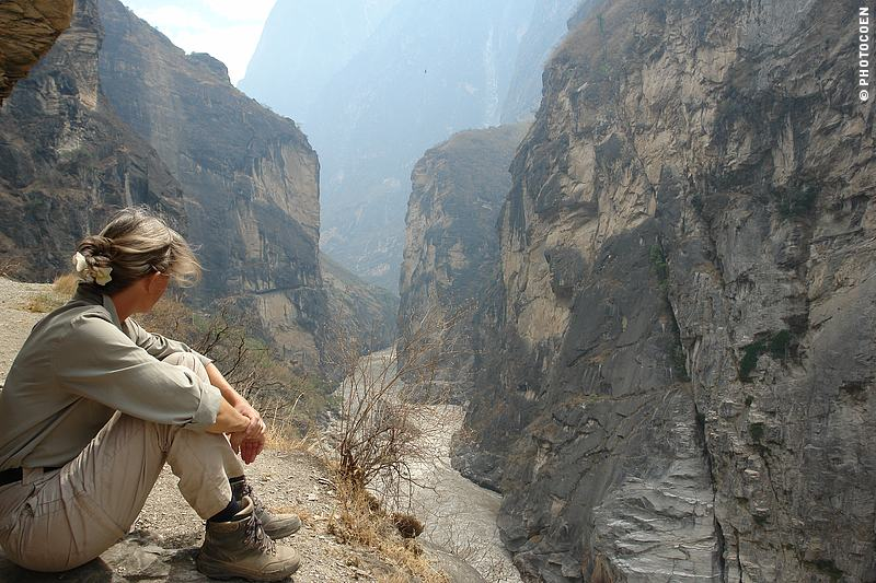 Hiking the Tiger Leaping Gorge; here Karin-Marijke is sitting along the trail and staring into the gorge.